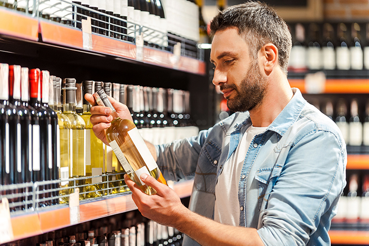 Legacy in a Glass - Side view of handsome young man holding bottle of wine and looking at it while standing in a wine store